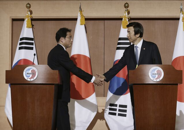 South Korean Foreign Minister Yun Byung-se, right, shakes hands with his Japanese counterpart Fumio Kishida after their joint press conference at Foreign Ministry in Seoul, South Korea, Monday, Dec. 28, 2015. The foreign ministers said they had reached a deal meant to resolve a decades-long impasse over Korean women forced into Japanese military-run brothels during World War II, a potentially dramatic breakthrough between the Northeast Asian neighbors and rivals