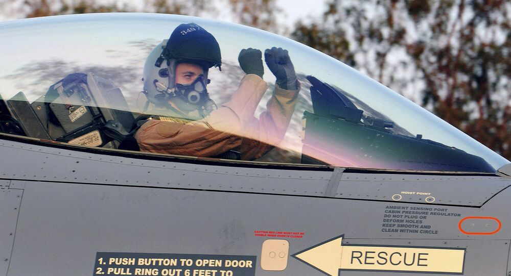 A Belgian pilot gestures as he sits in the cockpit of a F-16 fighter jet.