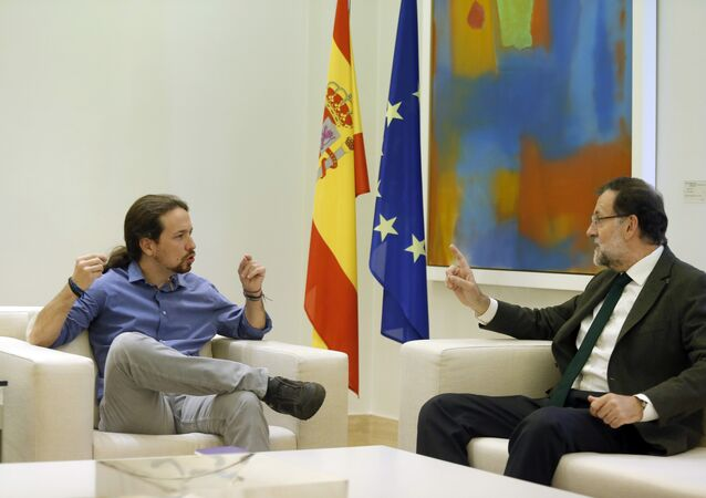 Spain's Prime Minister Mariano Rajoy, right, talks to Podemos party leader Pablo Iglesias during their meeting at the Moncloa palace, the Spanish premier's official residence, in Madrid.