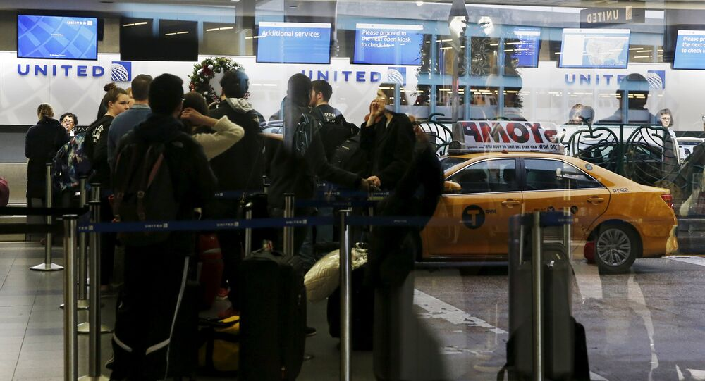 Air travelers are seen reflected through a window while waiting to check in for flights at LaGuardia Airport in New York