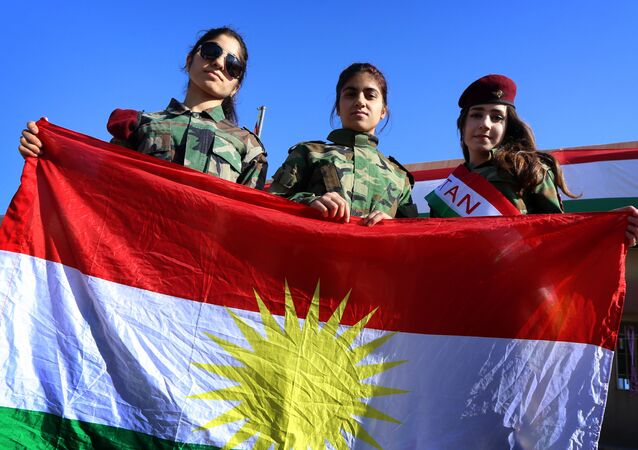 Iraqi Kurdish girls carry a Kurdistan flag during the celebration of Flag Day in the northern city of Arbil, the capital of the autonomous Kurdish region in northern Iraq
