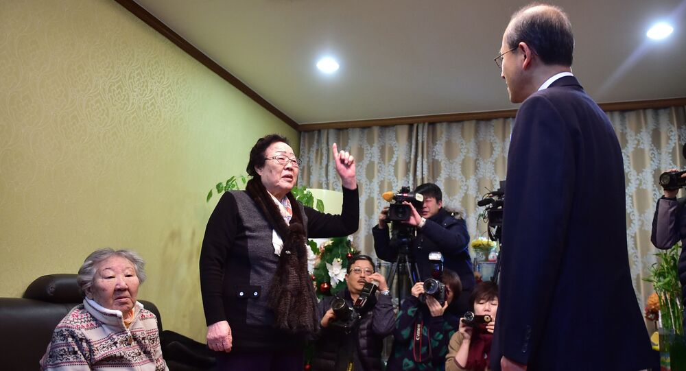 Former Korean sex slave Lee Yong-su, second from left, makes a gesture of protest at South Korean First Vice Foreign Minister Lim Sung-nam, right, during his visit to a shelter for women, who were forcibly recruited to work in Japanese wartime military brothels, in Seoul