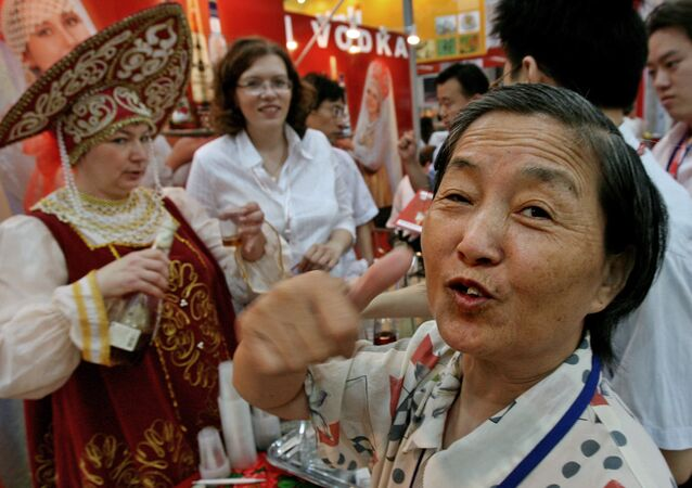 An elderly Chinese woman gives the thumbs up after tasting a vodka from Russia at a trade fair to promote Russian and International food products in Shanghai