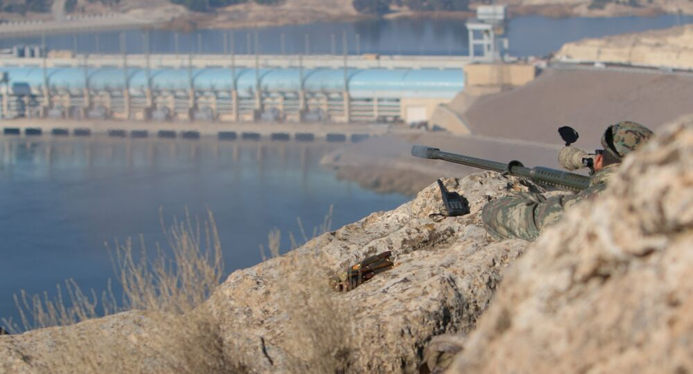 A sniper from the Democratic Forces of Syria takes an overwatch position at the top of Mount Annan overlooking the Tishrin dam, after they captured it on Saturday from Islamic State militants, south of Kobani, Syria December 27, 2015