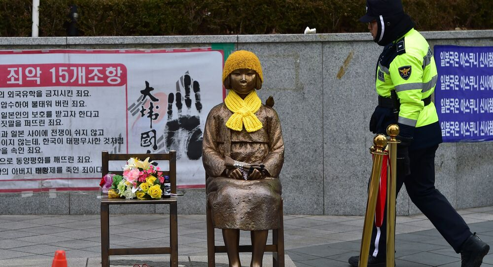 A South Korean policeman walks past a statue (C) of a teenage girl in traditional costume called the peace monument for former comfort women who served as sex slaves for Japanese soldiers during World War II, in front of the Japanese embassy in Seoul on December 29, 2015.