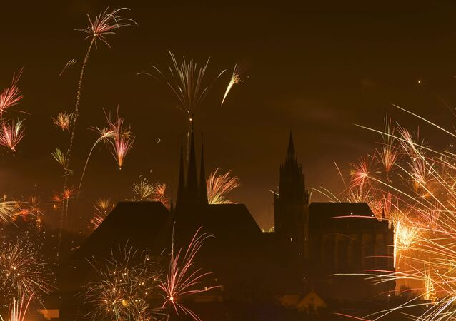 In this photo taken with long exposure, fireworks explode near the medieval Mariendom or St. Mary's Cathedral, right, and St. Severi's Church shortly after midnight during the New Year celebrations in Erfurt, central Germany, Friday, Jan. 1, 2016