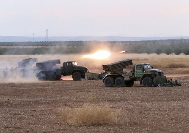 In this photo taken on Wednesday, Oct. 7, 2015, Syrian army rocket launchers fire near the village of Morek in Syria