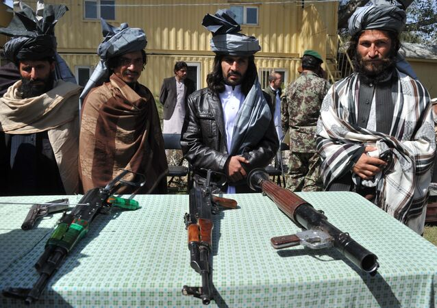 Former Taliban militants look on as they stand alongside their weapons in Jalalabad, the capital of Nangarhar province on March 19, 2014