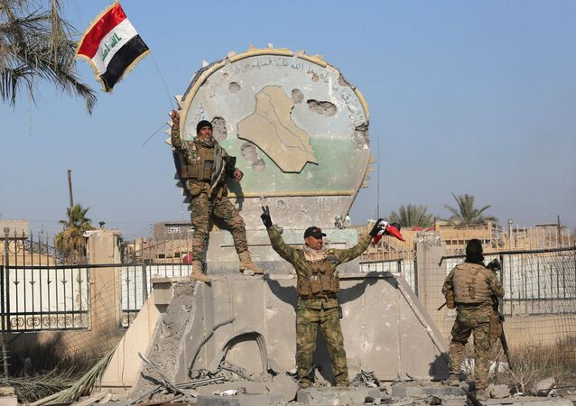 A member of the Iraqi security forces holds an Iraqi flag at a government complex in the city of Ramadi.