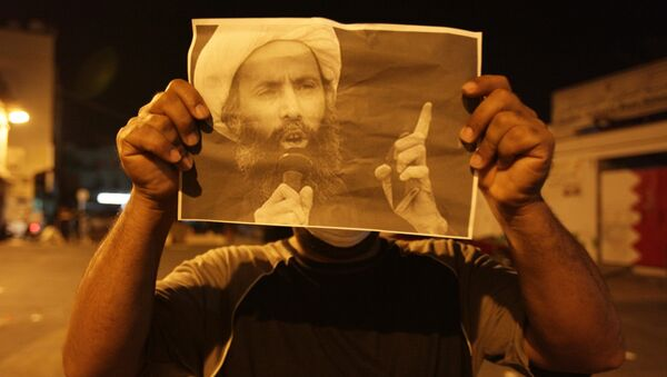 Bahraini anti-government protester holds up a picture of jailed Saudi Sheik Nimr al-Nimr during clashes with riot police in Sanabis, Bahrain, a suburb of the capital Manama - Sputnik International