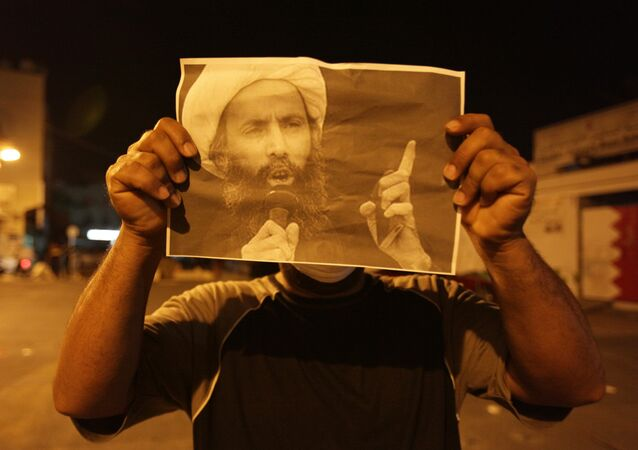 Bahraini anti-government protester holds up a picture of jailed Saudi Sheik Nimr al-Nimr during clashes with riot police in Sanabis, Bahrain, a suburb of the capital Manama