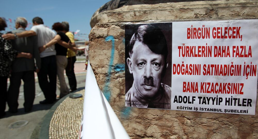 A depiction of Turkish Prime Minister Recep Tayyip Erdogan portraying him as Nazi leader Adolf Hitler is pasted on the front of Mustafa Kemal Ataturk's statue, founder of Turkey, at the Taksim square in Istanbul on Thursday, June 6, 2013