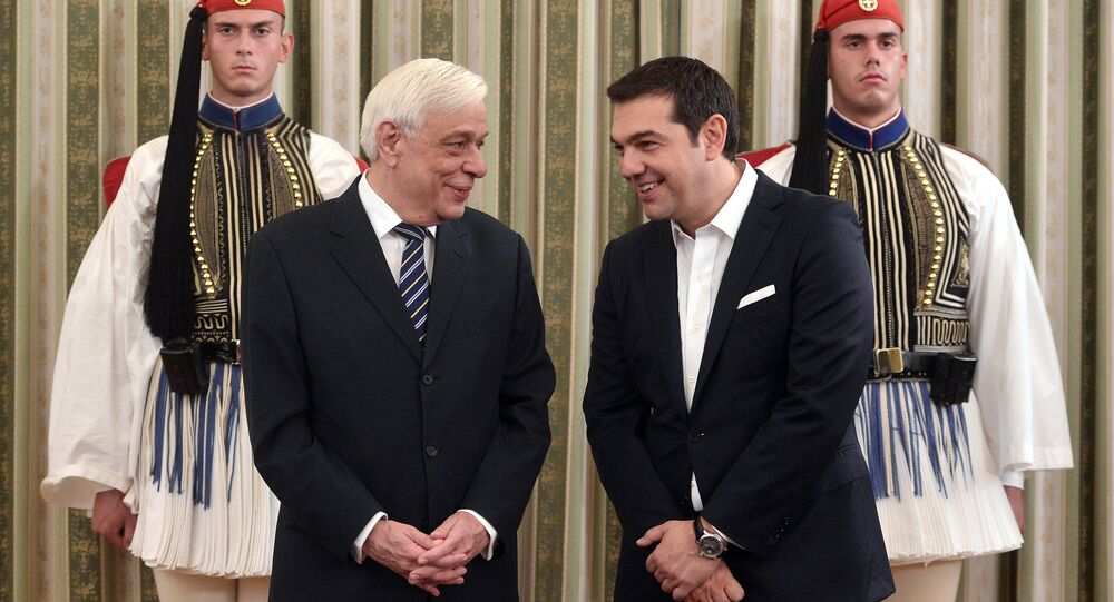 Greek Prime Minister Alexis Tsipras (R) chats with Greek President Prokopis Pavlopoulos as they attend the swearing-in ceremony of the new government at the presidential palace in Athens on September 23, 2015