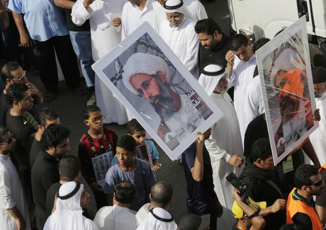 In this Saturday, May 30, 2015, photo, Saudis carry a poster demanding freedom for jailed Shiite cleric Sheikh Nimr al-Nimr, during a funeral procession, in Tarut, Saudi Arabia