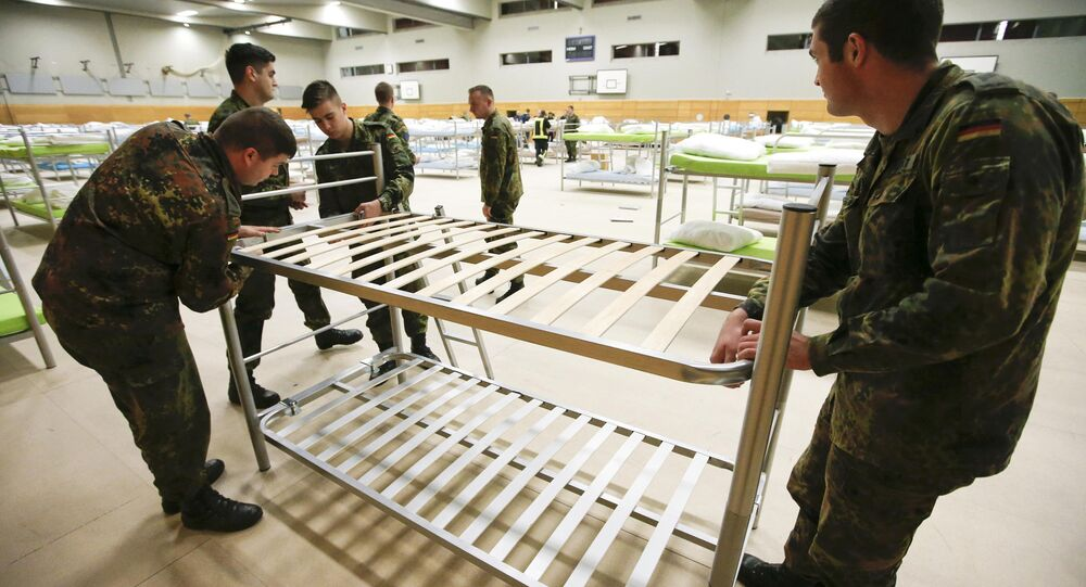 Soldiers from the guards battalion of the German armed forces Bundeswehr prepare beds as they transform the sports hall of the Jane-Addams high school into a refugee shelter in Hohenschoenhausen district in Berlin, Germany, December 8, 2015