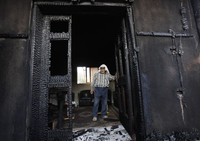 FILE - In this July 31, 2015 file photo, a Palestinian inspects a house after it was torched in a suspected attack by Jewish settlers, killing an 18-month-old Palestinian child and his parents, at Duma village near the West Bank city of Nablus