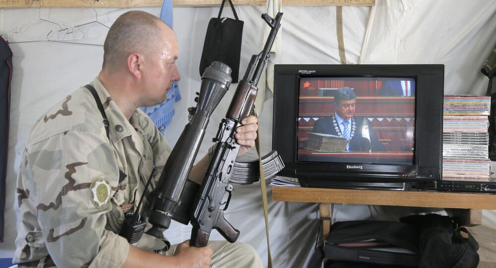 Ukrainian soldier watches the inauguration ceremony of Ukrainian President-elect Petro Poroshenko on TV in a tent at the Ukraine's Army position close to Slovyansk, Ukraine, Saturday, June 7, 2014