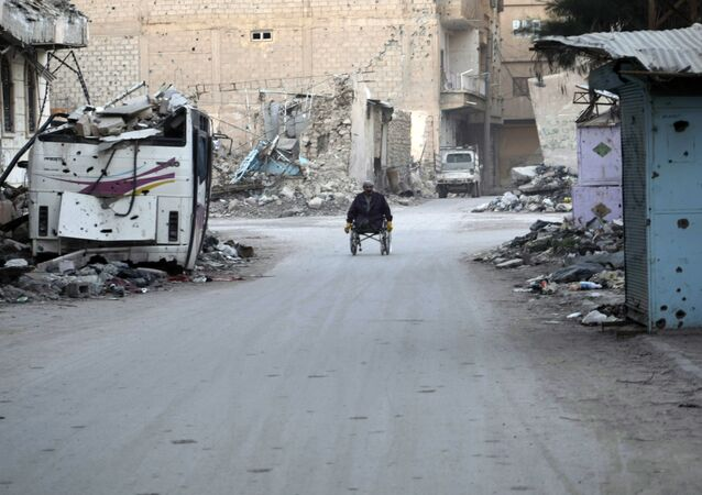 A man propels his wheelchair on February 13, 2014 in a devastated street in the Syrian eastern town of Deir Ezzor