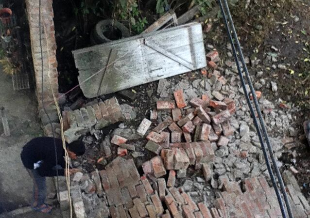 An Indian resident surveys a damaged wall at a house in Imphal on January 4, 2016