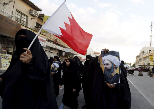 Protesters holding posters of Saudi Shi'ite cleric Nimr al-Nimr and a Bahraini national flag protest against his execution by Saudi authorities in the village of Sanabis, west of Manama, Bahrain January 3, 2016