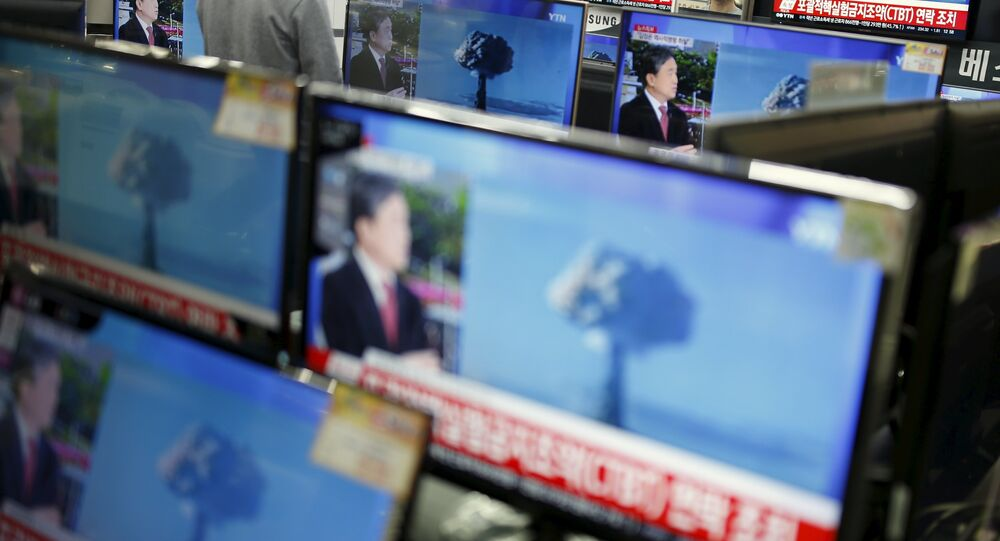 A sales assistant watches TV sets broadcasting a news report on North Korea's nuclear test, in Seoul, January 6, 2016