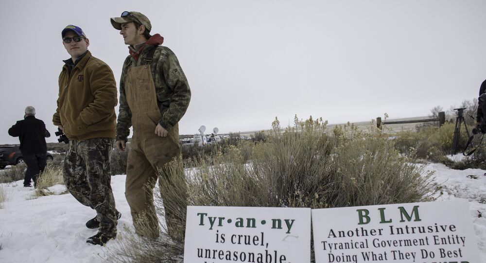 Members of an armed anti-government militia, monitor the entrance to the Malheur National Wildlife Refuge Headquarters near Burns, Oregon.