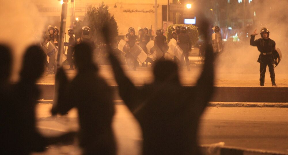 Egyptian protesters gesture as they clash with riot police at Cairo's landmark Tahrir Square on November 19, 2011, as Egyptian police fired rubber bullets and tear gas to break up a sit-in among whose organisers were people injured during the Arab Spring which overthrew veteran president Hosni Mubarak
