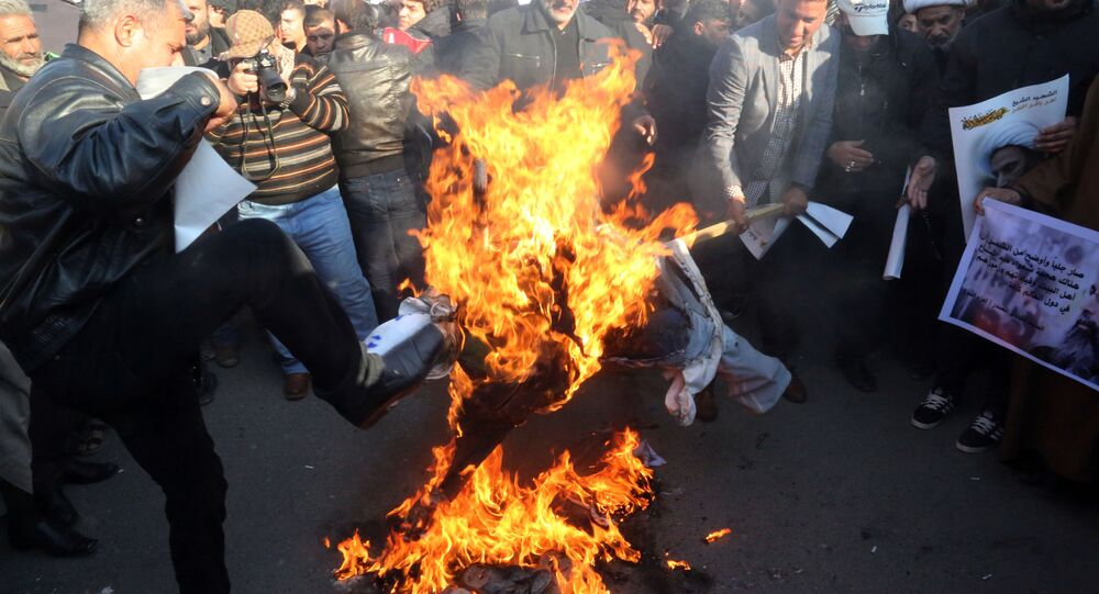 Followers of Shiite cleric Muqtada al-Sadr burn an effigy of King Salman of Saudi Arabia as they hold posters of Sheik Nimr al-Nimr during a demonstration in Baghdad, Iraq.