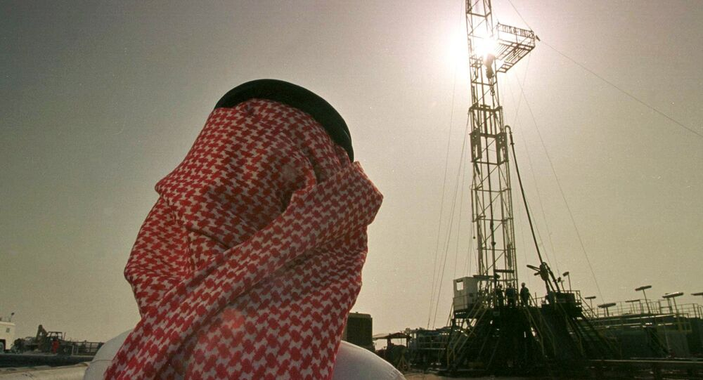 An official of the Saudi oil company Aramco watches progress at a rig at the al-Howta oil field.