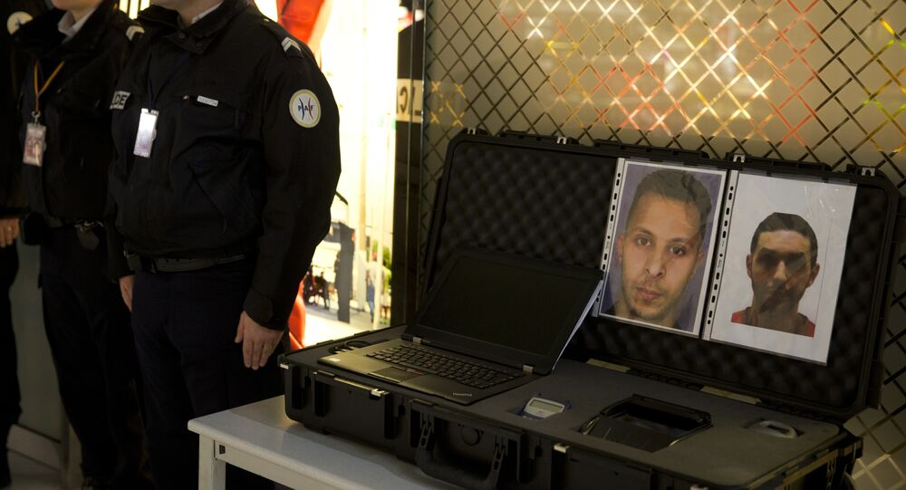 Police officers stand next to the wanted notice of terrorist Salah Abdeslam (L) and Mohamed Abrini on December 3, 2015 at the Roissy-Charles-de-Gaulle airport in Roissy-en-France, outside Paris