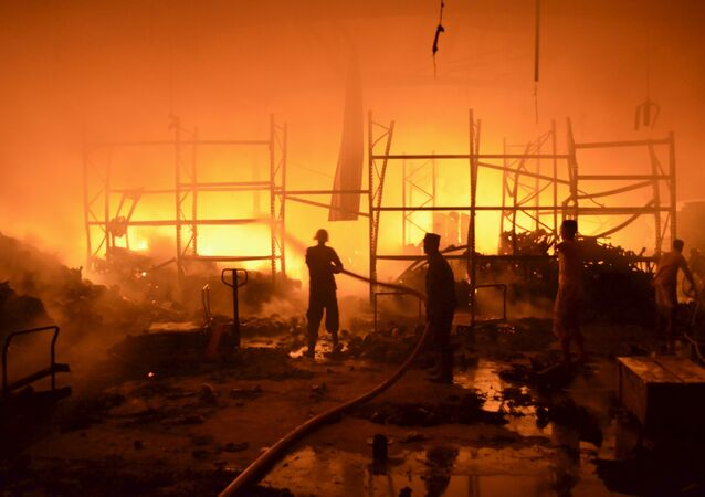 Firefighters attempt to extinguish a fire at a foodstuff storage facility destroyed by a Saudi-led air strike in Yemen's Red Sea port city of Houdieda January 6, 2016.