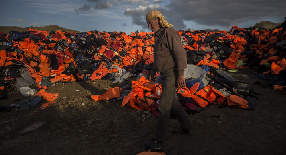 A man walks across piles of life jackets used by refugees and migrants to cross the Aegean sea from the Turkish coast.