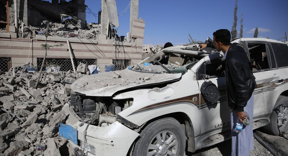 A man inspects his car damaged by Saudi-led airstrikes in Sanaa, Yemen, Friday, Jan. 8, 2016