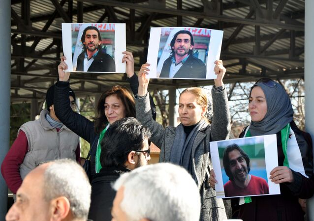 Women hold pictures of film maker Naji Jerf, who was killed on December 27, during his funeral in Gaziantep on December 28, 2015