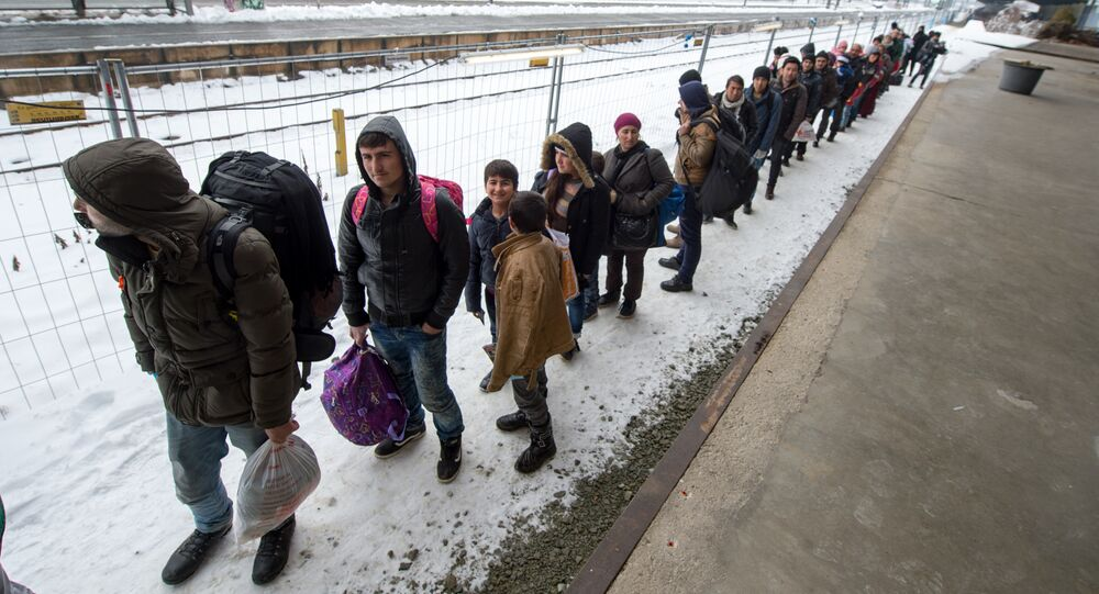 Refugees walk to a chartered train at the railway station of Passau, Germany Tuesday Jan. 5, 2016.