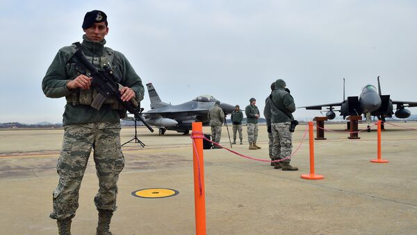 A US soldier (L) stands guard near a US F-16 fighter jet (C) and a South Korea F-15K fighter jet (R) before a press briefing on the flight by a US B-52 Stratofortress over South Korea at the Osan Air Base in Pyeongtaek, south of Seoul, on January 10, 2016 - Sputnik International