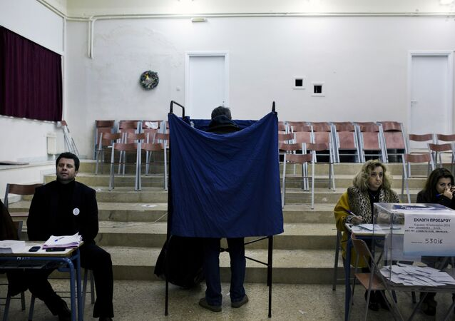 A man prepares his vote in a voting booth prior to casting his ballot in an election for the leadership of Greece's conservative New Democracy party, at a polling station in Athens on January 10, 2016