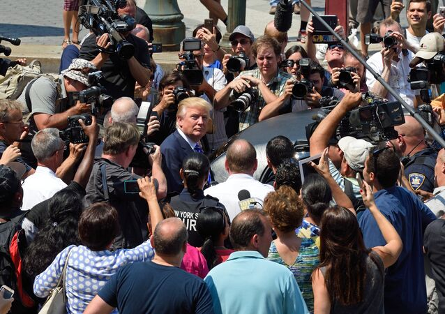 US presidential candidate Donald Trump(C) is mobbed by the media as he exits New York Supreme Court after morning jury duty August 17, 2015 in New York