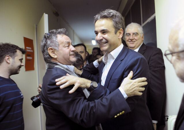 Kyriakos Mitsotakis (c-R), the new elected leader of Greece's conservative New Democracy party, hugs a supporter during his exit from his office in Athens, after winning the party elections, Greece, January 11, 2016