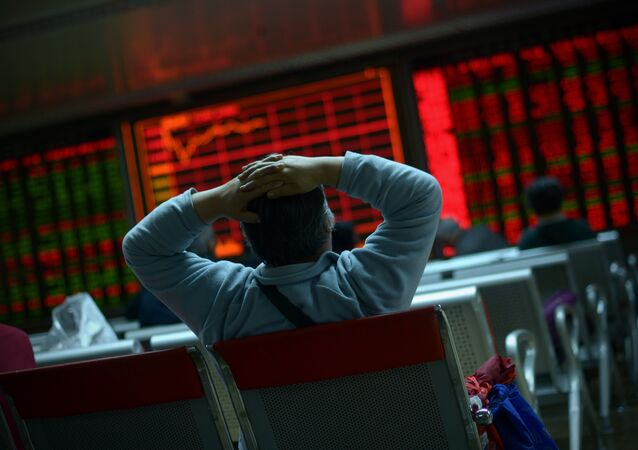 An investor looks at screens showing stock market movements at a securities company in Beijing on January 8, 2016