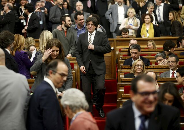 Incoming Catalan President Carles Puigdemont (C) adjusts his jacket during the investiture session at the Catalunya Parliament in Barcelona, Spain, January 10, 2016