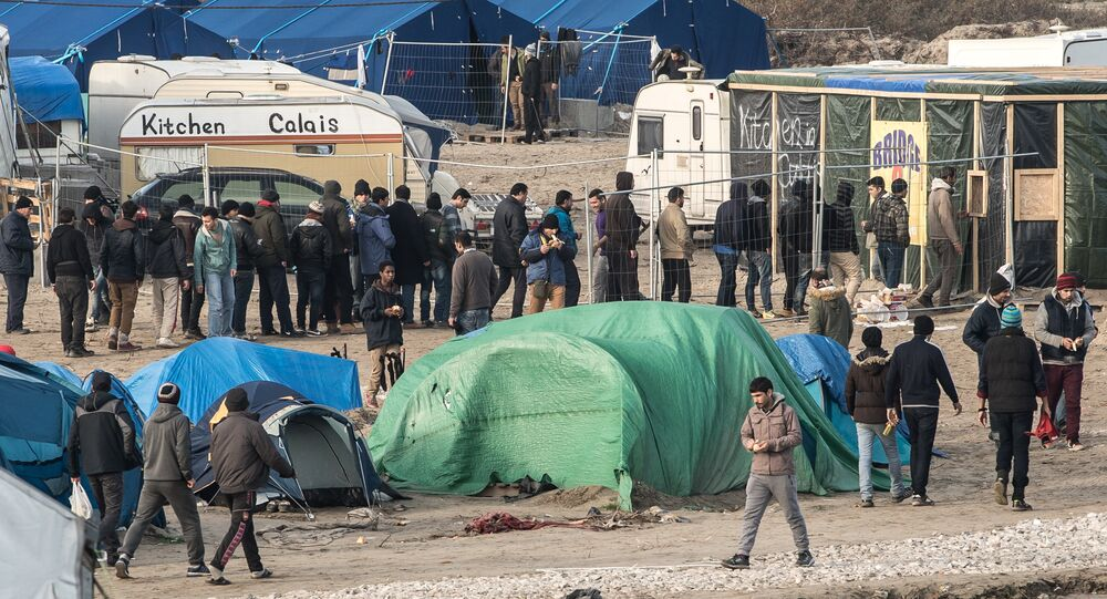 People walk at the migrant camp known as the Jungle in Calais on December 7, 2015
