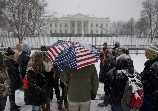 A light snow falls on a tour group outside the White House in Washington, Tuesday, Jan. 6, 2015, as temperatures hover around freezing