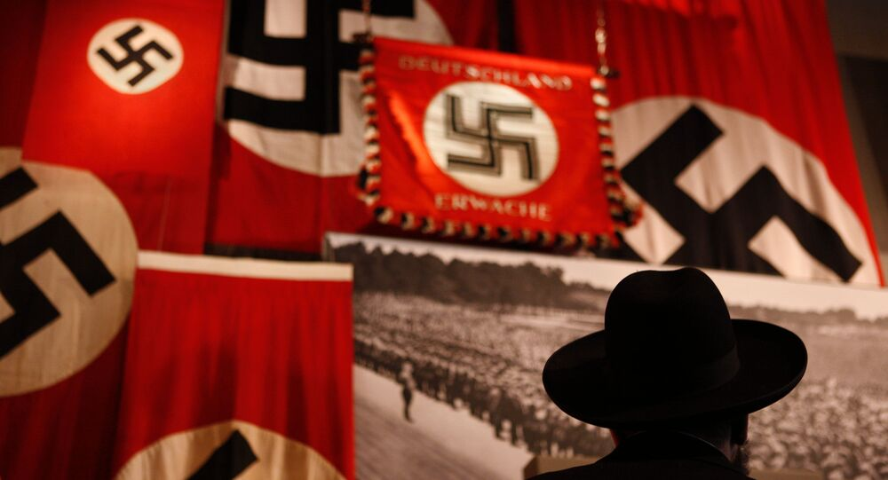 A man looks at exhibit showing the Nazi flags.