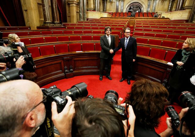 Incoming Catalan President Carles Puigdemont, center left, shakes hands with outgoing Catalan President Artur Mas after the investiture session at the Catalonian parliament in Barcelona, Spain, Sunday, Jan. 10, 2016.