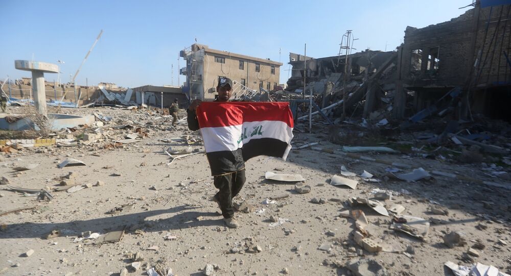A member of the Iraqi security forces holds his national flag on December 28, 2015 at the heavily damaged government complex after they recaptured the city of Ramadi, the capital of Iraq's Anbar province, about 110 kilometers west of Baghdad, from Islamic States group jihadists