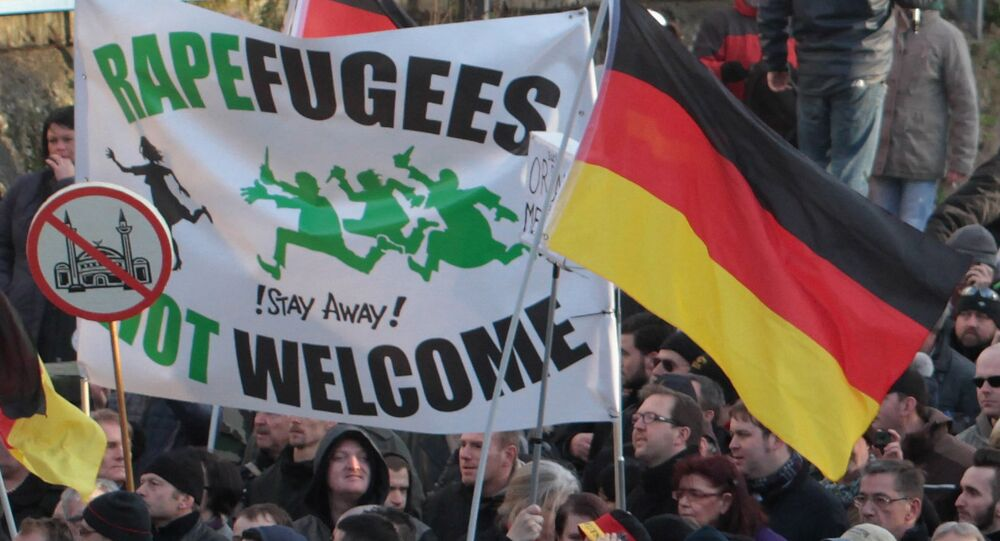 Right-wing demonstrators hold a sign Rapefugees not welcome - !Stay away! and a sign with a crossed out mosque as they march in Cologne, Germany Saturday Jan. 9, 2016