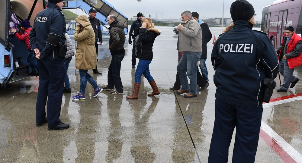 Police officers escort rejected refugees who are boarding an aircraft at the airfield of the Franz-Josef-Strauss airport in Munich, southern Germany, on December 9, 2015, as the plane brings rejected asylum seekers back to their country