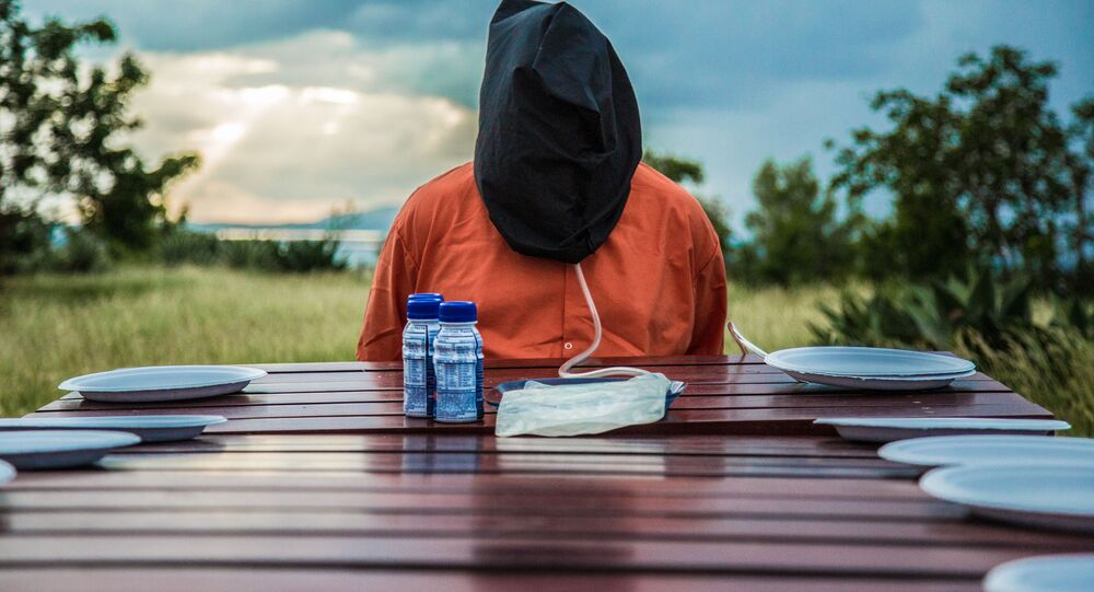 A hooded activist attached to a force-feeding apparatus meant to remind viewers of the actual devices used in the Guantanamo detention center.