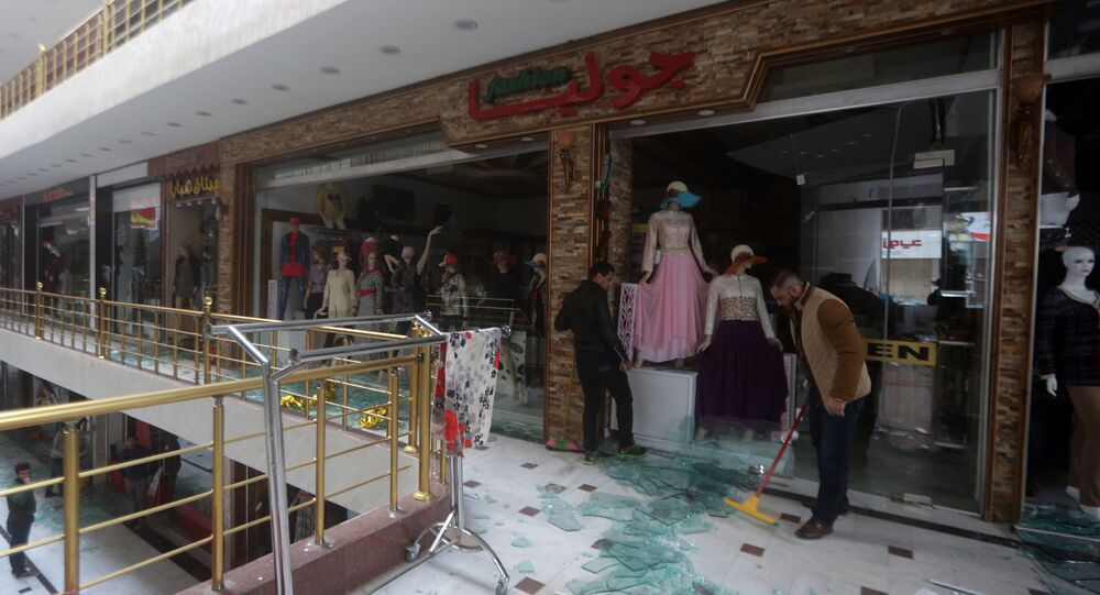 Iraqi men clean up the damage at the al-Jawaher mall in eastern Baghdad the day after a bomb attack on January 12, 2016